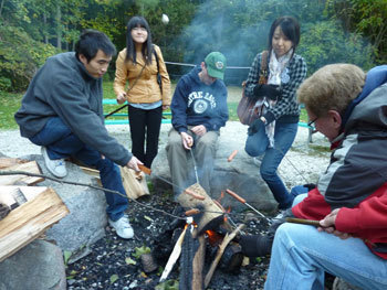 ESL students roasting marshmallows over an open fire